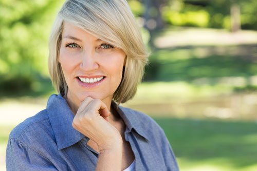 Woman outside smiling with hand to her chin illustrating how Botox® at our Centennial practice enhances your overall look
