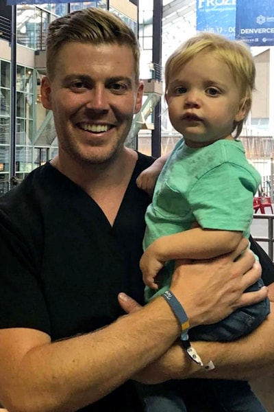 Dr. Andrew Cote, an Invisalign® dentist in Centennial, CO holding his toddler son