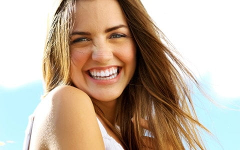 Woman smiling outside - cosmetic dentistry
