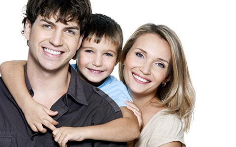 Family of 3 hugging and smiling - family dentistry