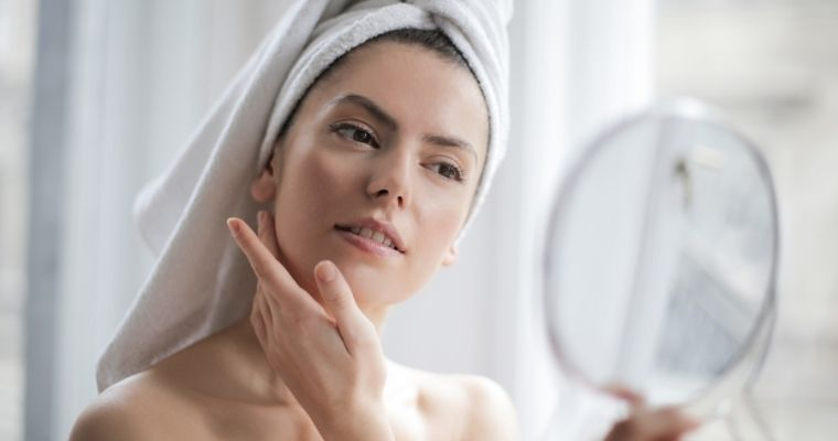 A woman examining her Botox treatment in the mirror